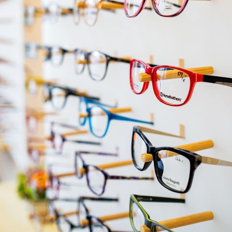 Rôznofarebné okuliare vystavené na stojane