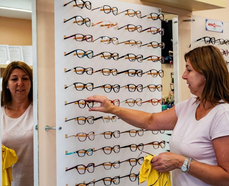 Zaměstnankyně optiky Optika ERIMA čistí brýle na stojanu